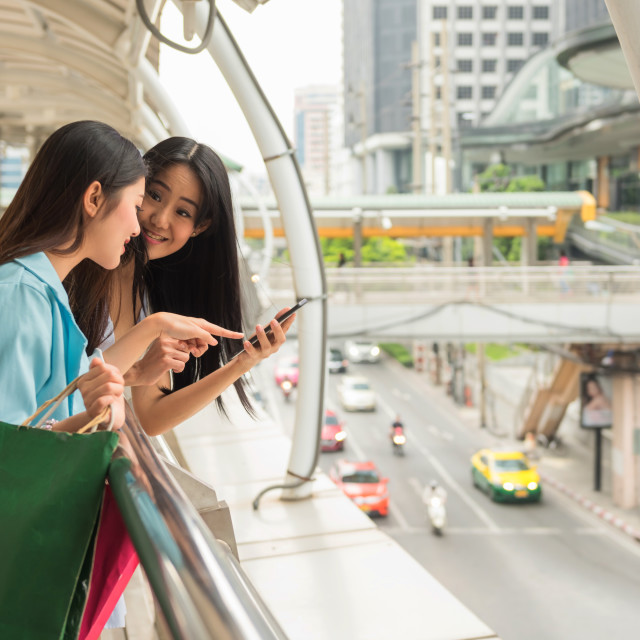 """Happy girls check store location by smartphone"" stock image"