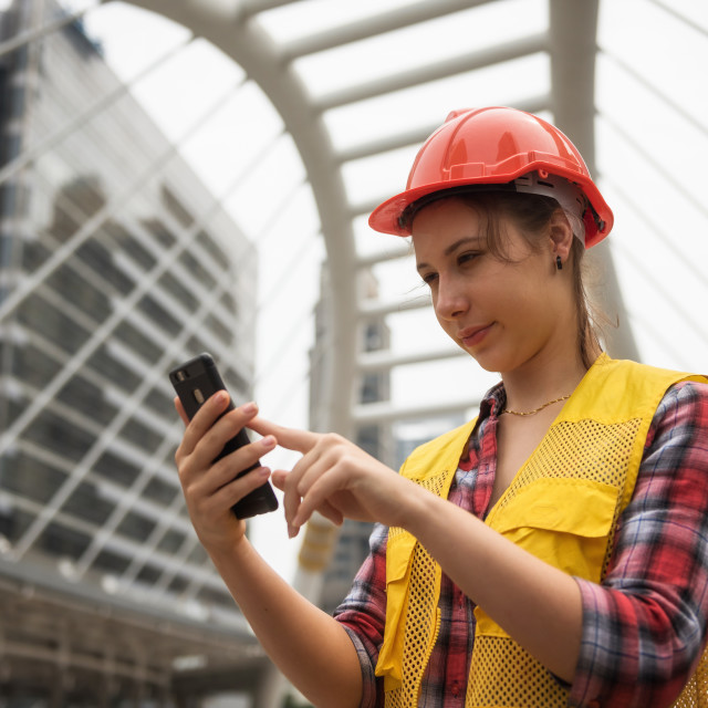 """American female engineer using smartphone at site"" stock image"