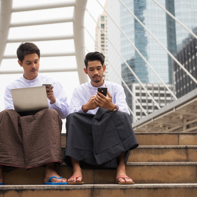 """Burmese businessmen use smartphone in city"" stock image"