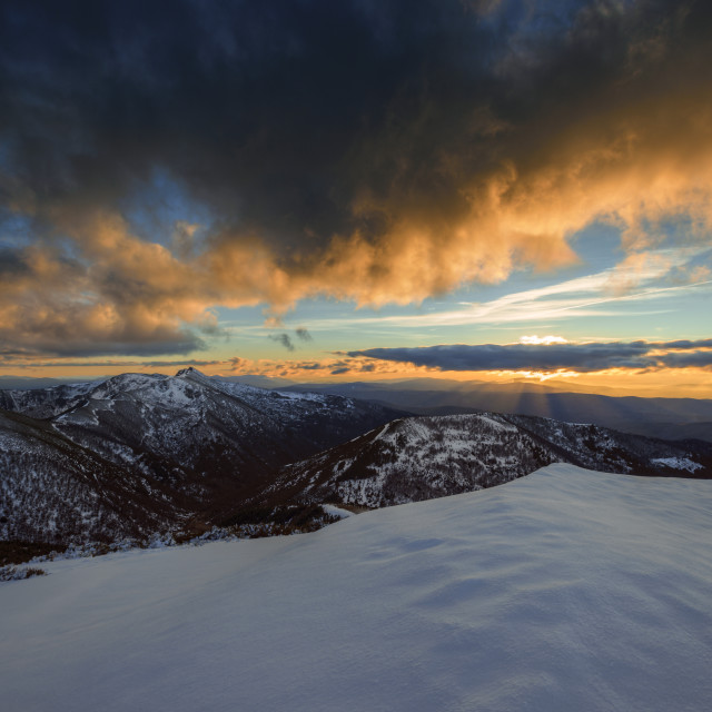"""""""Golden clouds by the sunset light over snowy mountains"""" stock image"""