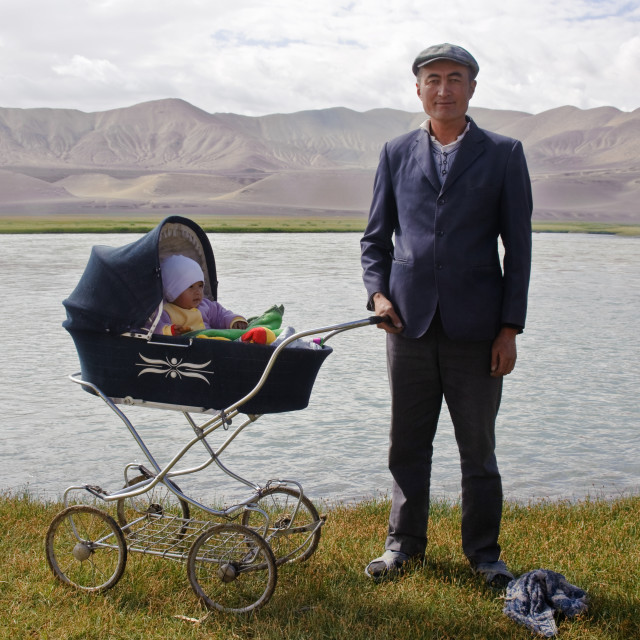 """Father taking a walk with his infant ( Pamir plateau, Tajikistan)"" stock image"