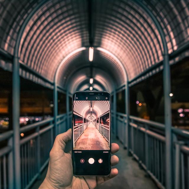 """Man hand holding mobile phone capturing bridge"" stock image"