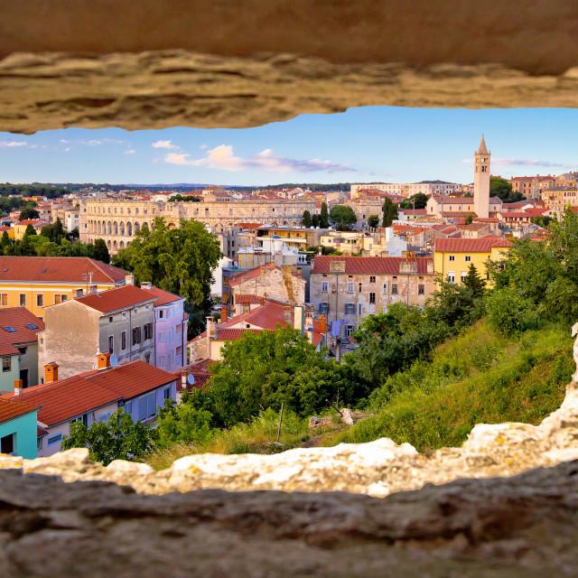 """Panoramic view of Pula landmarks through stone window"" stock image"