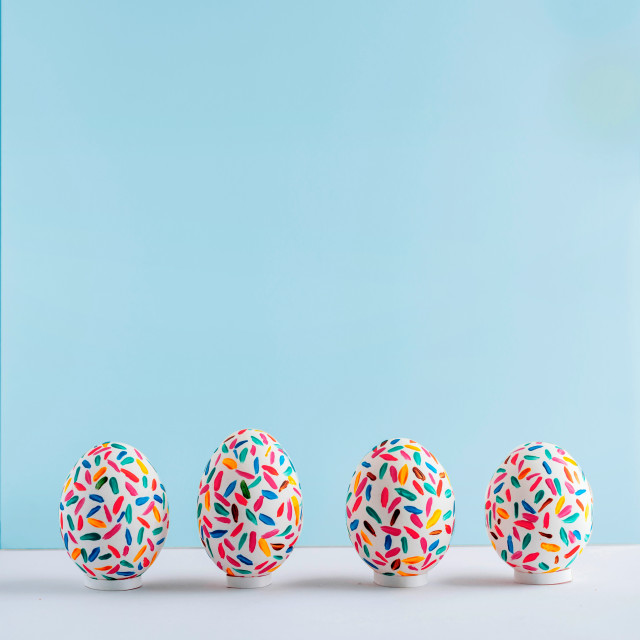 """""""Funny multicolored easter eggs hand painted on soft blue background, front..."""" stock image"""