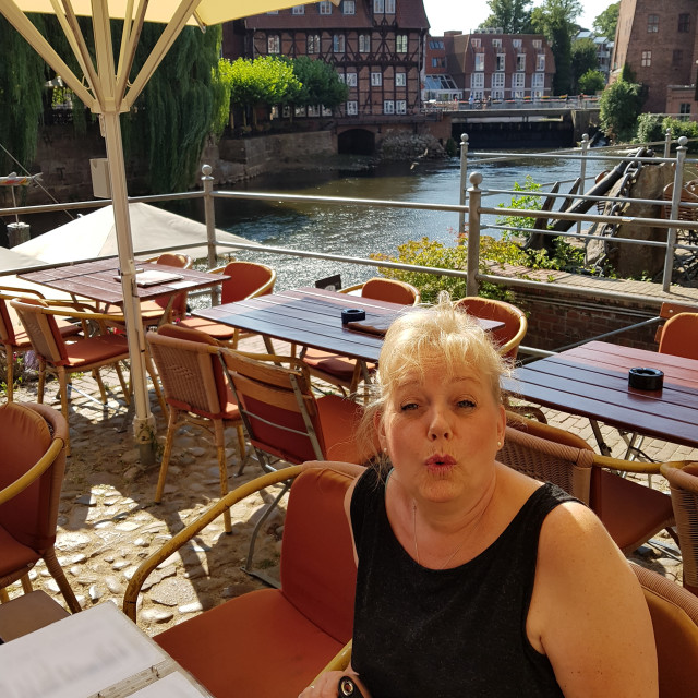"""Woman sitting on the terrace of a restaurant in Lueneburg."" stock image"