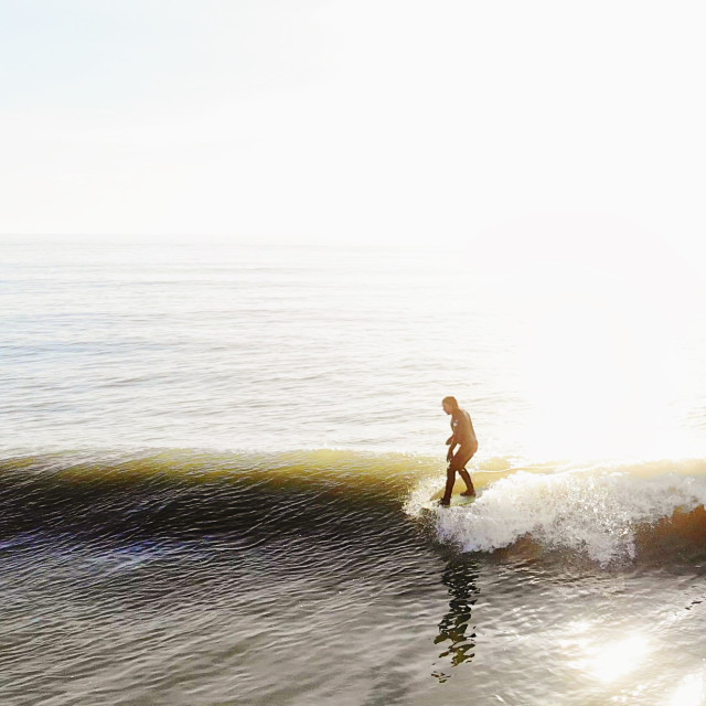 """""""A surfer on a longboard hanging five on a colourful wave"""" stock image"""