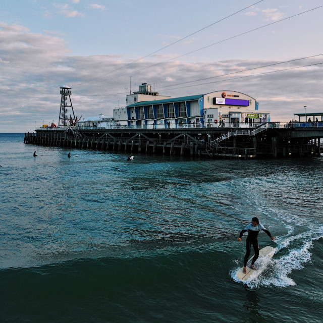 """""""A surfer on a longboard hanging five at Bournemouth pier"""" stock image"""