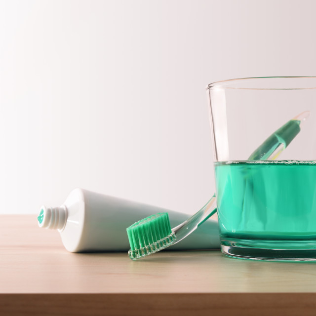 """""""Toothbrush toothpaste and mouthwash on the wooden table front view"""" stock image"""