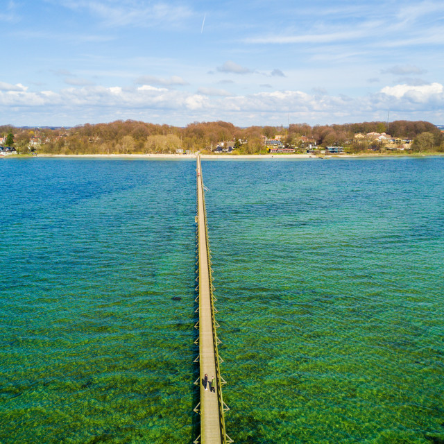 """""""Aerial view of the endless pier that goes into the ocean with a shore on the..."""" stock image"""