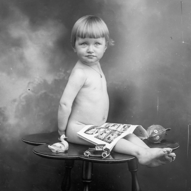 """""""VINTAGE PORTRAIT OF A BABY WITH TOYS AND NEWSPAPER COMICS"""" stock image"""