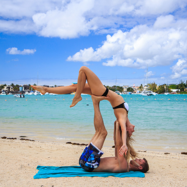 """""""Young couple boy and girl practicing acroyoga exercises in the morning on the..."""" stock image"""