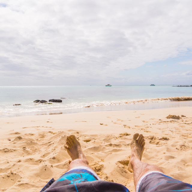 """Close up of a young man feet relaxing on the beach with the sea in the..."" stock image"