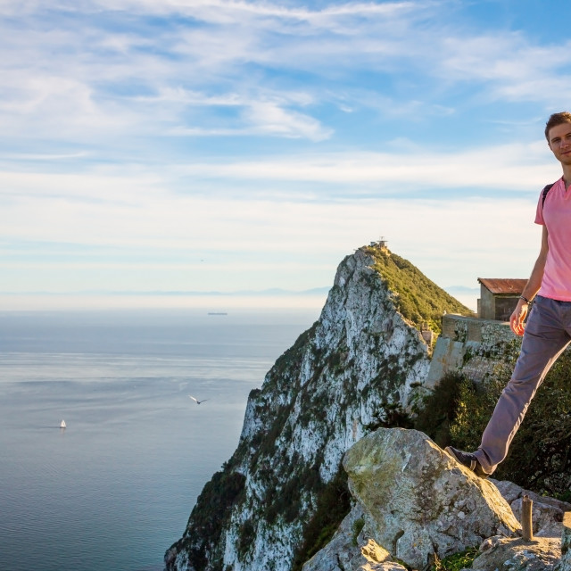 """Lonely man standing on the edge on the top of the cliff watching over..."" stock image"