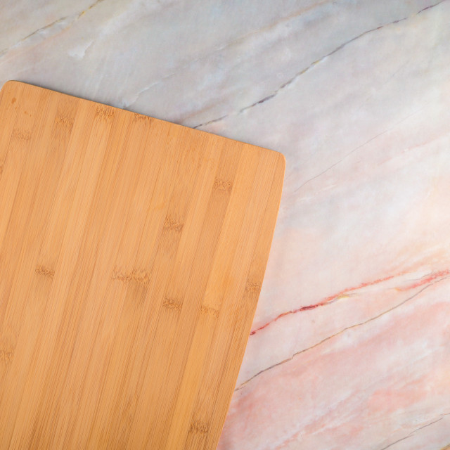 """Wooden cutting board on a gray marble background"" stock image"