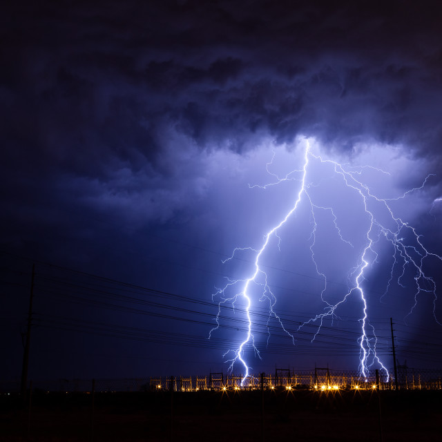 """Lightning bolts strike an electrical substation during a storm."" stock image"