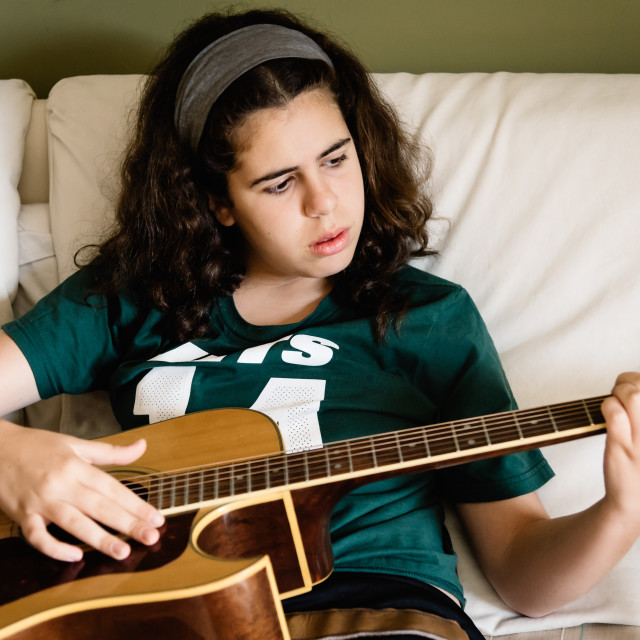 """""""Girl practicing chords on acoustic guitar"""" stock image"""