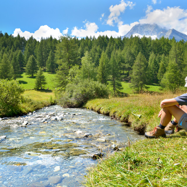 """""""hiker sitting at the edge of a river"""" stock image"""