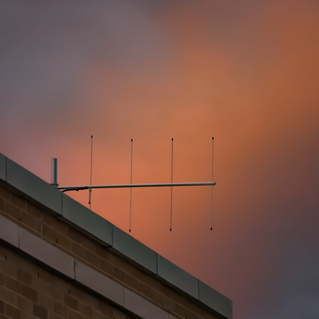 """TV ANTENNA AGAINST CLOUDS ORANGE IN THE SETTING SUN"" stock image"