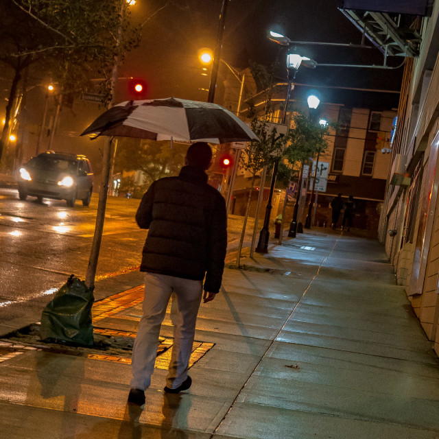 """MAN WITH UMBRELLA, RAINY NIGHT IN THE CITY"" stock image"