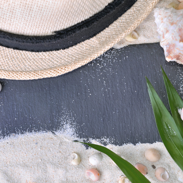 """""""empty black slate on the sand with hat and shells"""" stock image"""