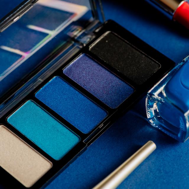 """""""Blue set of eyeshadows lipsticks and nailpolishes and eyeliners on blue..."""" stock image"""