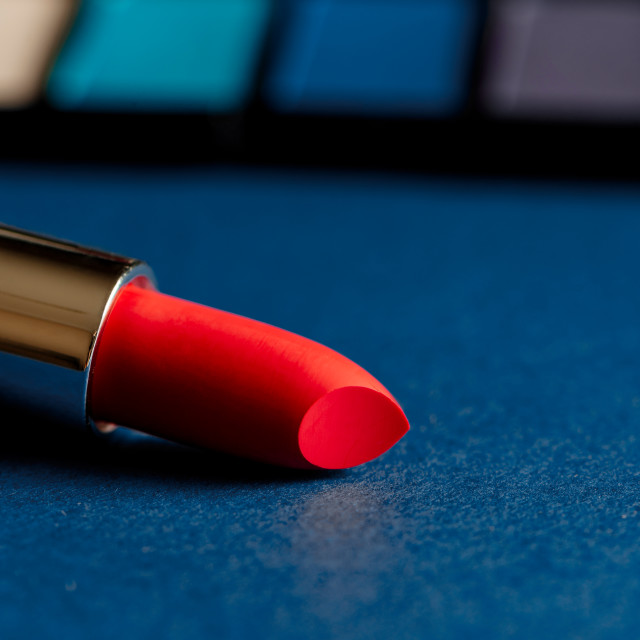 """""""Pink lipstick and blue eyeshadow palette and blue background"""" stock image"""