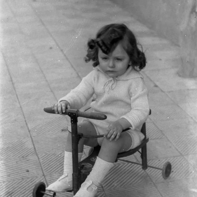 """""""VINTAGE PORTRAIT OF LITTLE GIRL RIDING A WHEELED TOY"""" stock image"""
