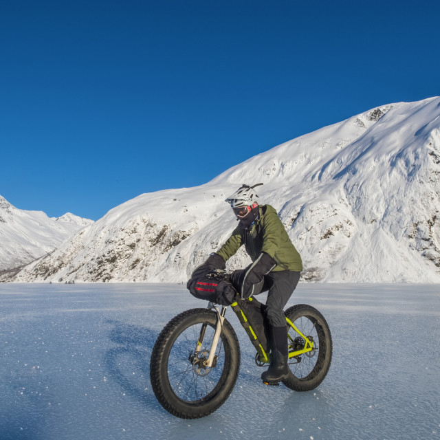 """""""A man riding his fatbike across frozen Portage Lake in mid-winter in..."""" stock image"""