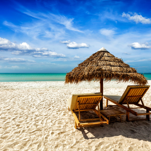 """""""Two lounge chairs under tent on beach"""" stock image"""