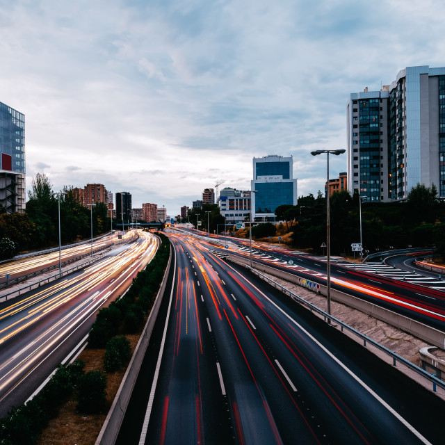 """Motorway with light trails at dusk against cityscape"" stock image"