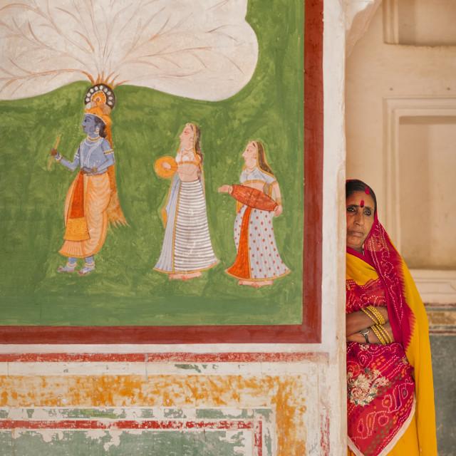 """Portrait Hindu women standing next to art work inside Amer Fort, Jaipur."" stock image"