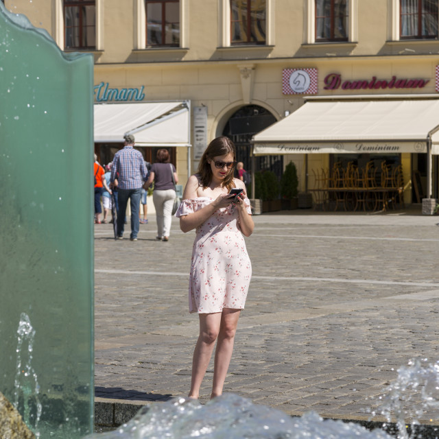 """""""Wroclaw, Poland - July 09, 2018: A young girl with a smartphone near the fountain on the market square in Wroclaw, Poland"""" stock image"""