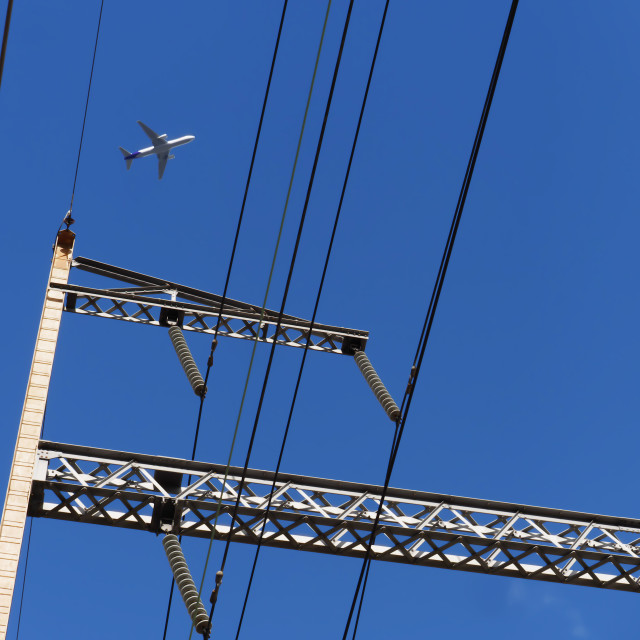 """Jet flying over the train station power lines"" stock image"