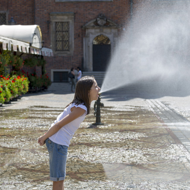 """""""Wroclaw, Poland - July 09, 2018: A girl in front of a fountain in the Market Square of Wroclaw, Poland."""" stock image"""