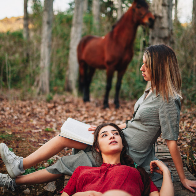 """""""Young women reading a book and taking photos in the forest"""" stock image"""