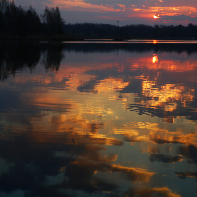 """""""Sunrise over the lake reflected on the water surface."""" stock image"""