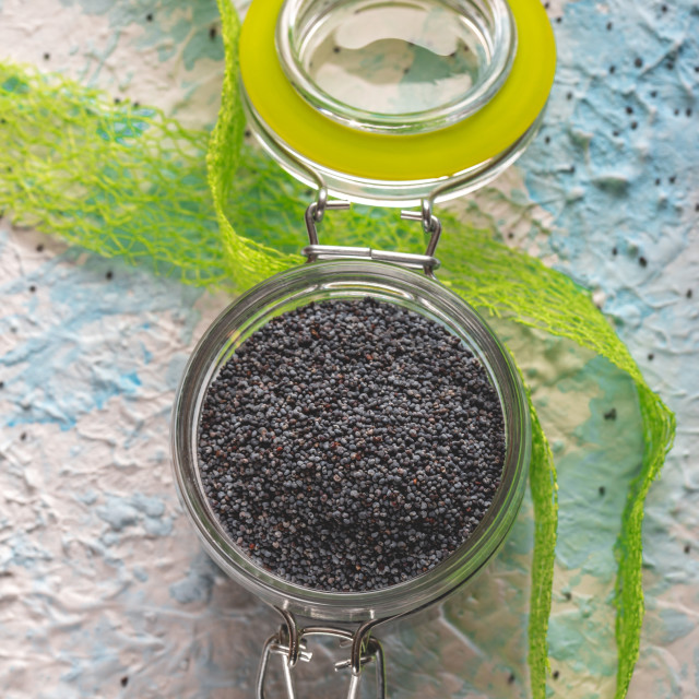"""""""Glass jar with sealed cover full of raw poppy seeds on light board"""" stock image"""