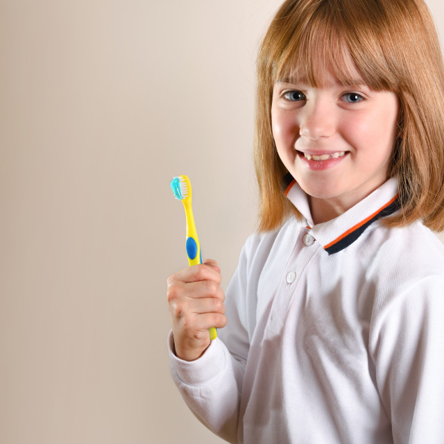 """Girl on side showing tooth brush on isolated brown"" stock image"