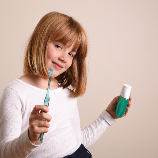 """Girl showing toothbrush and toothpaste on brown isolated background"" stock image"
