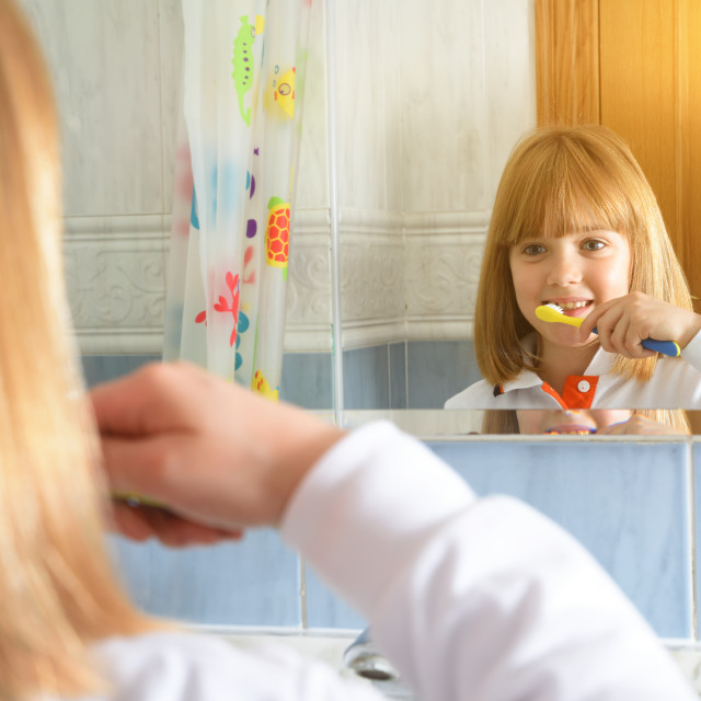 """Little girl cleaning her teeth looking at mirror in bathroom"" stock image"