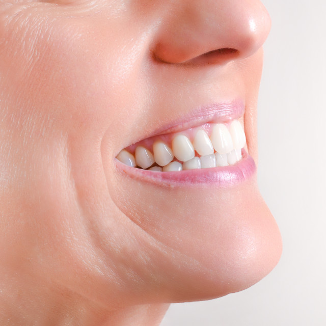 """Mature woman showing perfect natural white teeth half profile"" stock image"