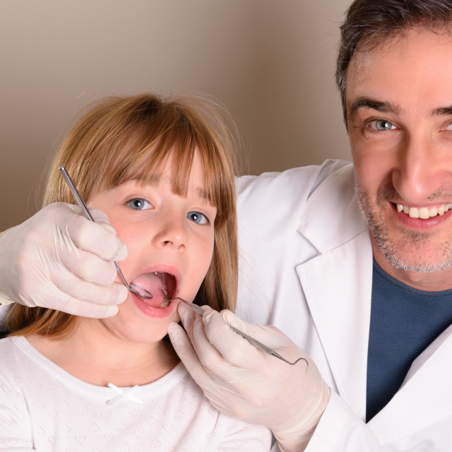 """Smiling pediatric dentist checking the mouth of a girl"" stock image"