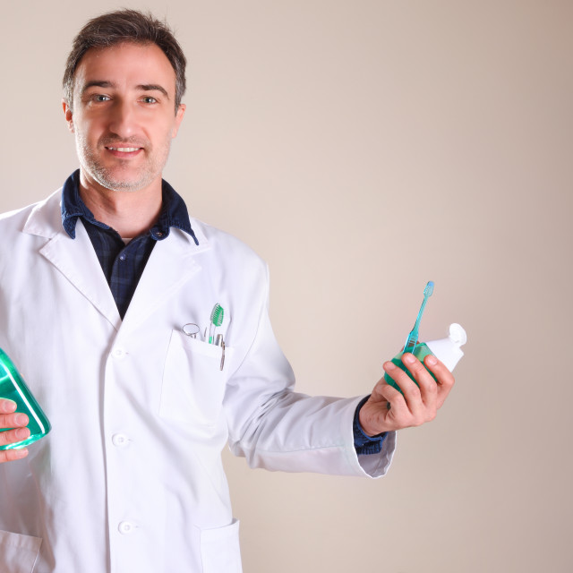 """Uniformed dentist with products in the hands general view"" stock image"