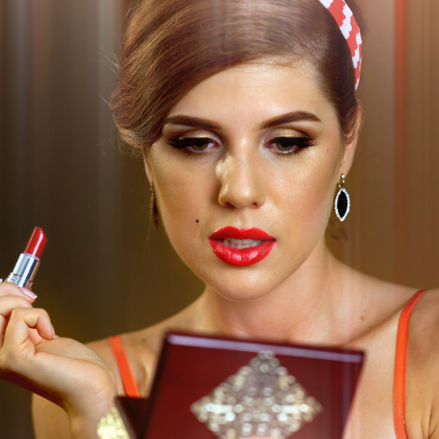 """""""Woman looking mirror and apply shiny red lipstick"""" stock image"""