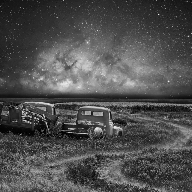 """""""Two abandoned vintage trucks parked beside a trail in a field under a star filled sky in a rural countryside landscape"""" stock image"""
