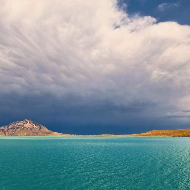 """""""Beautiful aqua water with mountains and a valley in the distance under a cloudy blue sky in a summer Wyoming landscape"""" stock image"""
