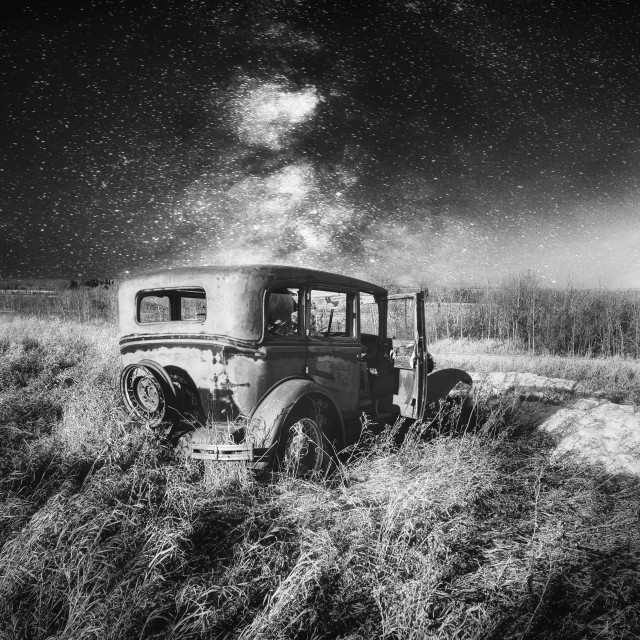 """""""A vintage four door car with one door open abandoned in tall grass under a star filled night sky in a black and white landscape"""" stock image"""
