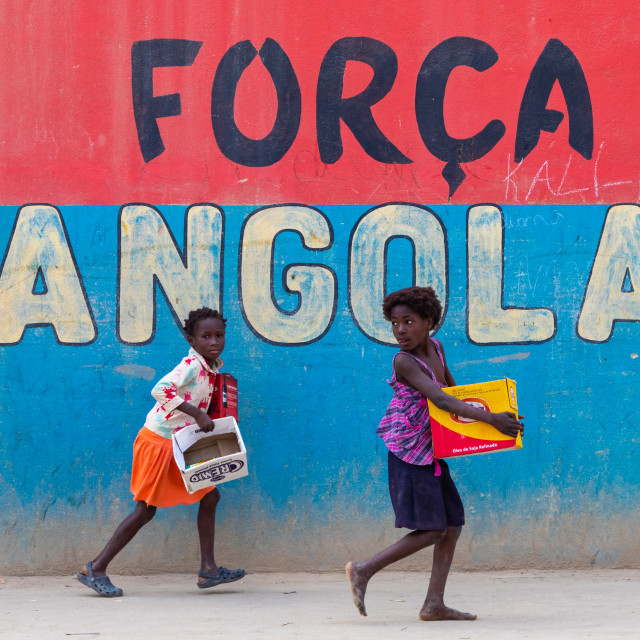 """Angolan girls in front of a patriotic slogan on a wall, Benguela Province,..."" stock image"