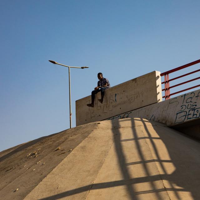 """""""Angola man sit on the side of the road, Benguela Province, Catumbela, Angola"""" stock image"""