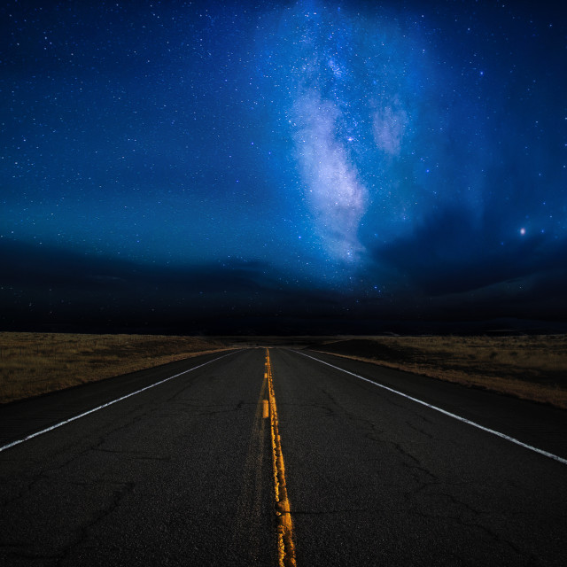 """""""A highway disappearing into the distance illuminated by a star filled dramatic night sky in a rural landscape"""" stock image"""